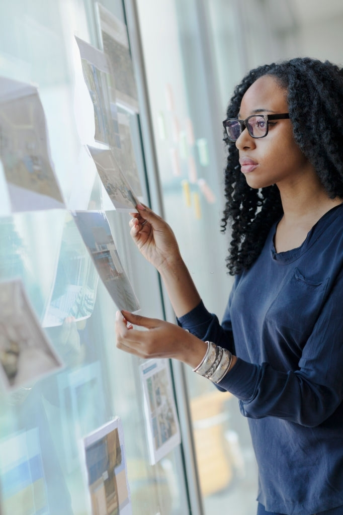 Young Black female woman designer creative looking at designs diagrams interior drawings taped to glass wall window choosing opportunities eyeglasses casual bright daylight in startup office urban planning company curly hair